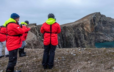 Hurtigruten passengers who enthusiastically admire the magnificent view of the cliffs along the coast of Bjørnøya. The experience ends up in great photographs and memories for a lifetime.