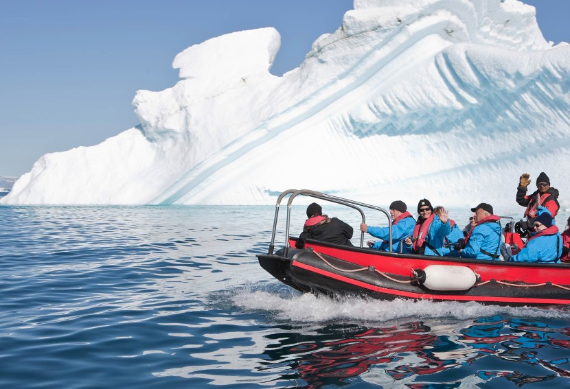 A group of people riding on the back of a boat in the water